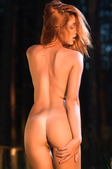 Hot redhead Michelle H wanders through lush countryside with her camera